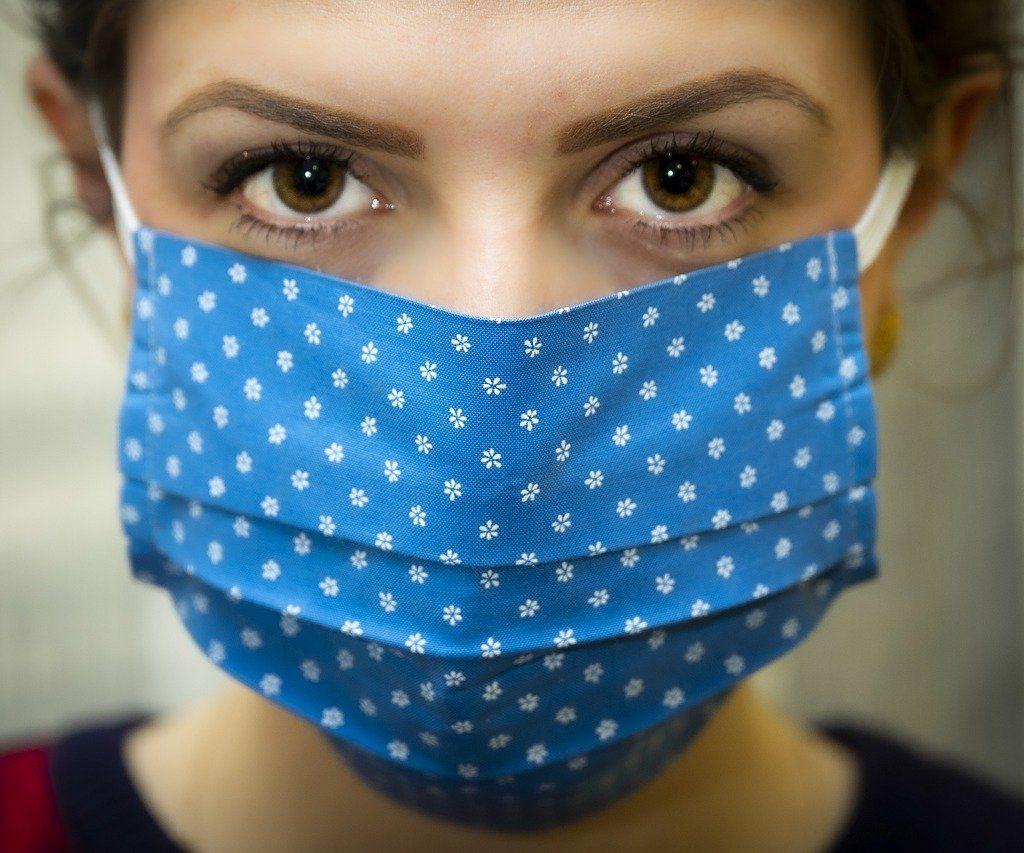 Jonge vrouw met blauw mondkapje tegen besmetting van het covid19 virus, corona.